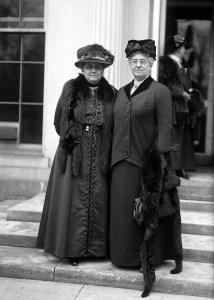 Jane Addams and Mary McDowell stand outside a building on the steps. They wear hats and look powerful.