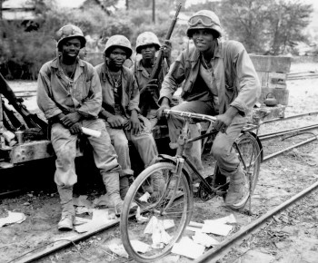 """""""Negro Marines, attached to the Third Ammunition Company, take time out from supplying ammunition to the front line on Saipan."""