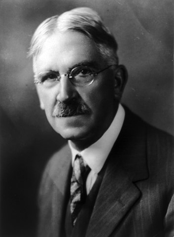 Portrait of John Dewey. He wears glasses and has a mustache