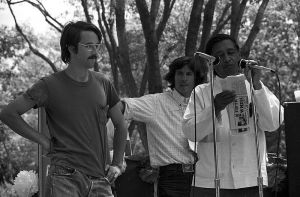 Duncan West speaking at a rally with Cesar Chavez. They stand at microphones