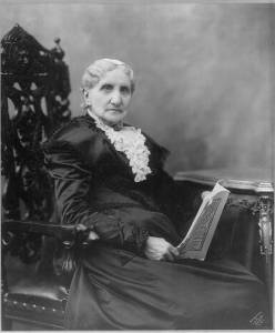 Mary Ashton Livermore sits in a chair. Her hair is white and she wears lace at her neck.