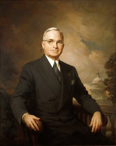 Painting of Truman with the U. S. Capitol visible in the background. He is seated.