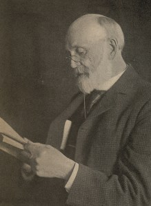 William Lloyd Garrison wearing glasses, holds a book in his hands. He is older with a white beard and balding head.