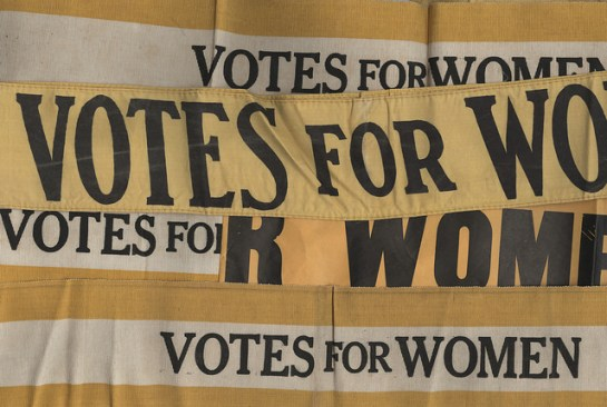 "Suffrage banners say ""Votes for Women"""