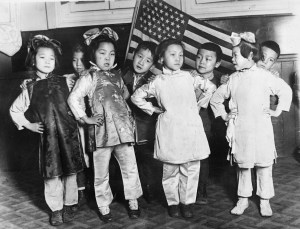 Chinese children in native costume stand before an American flag.