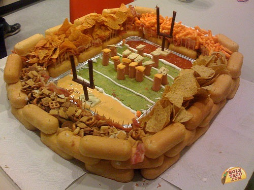 A stadium made out of unhealthy food: Twinkie bleackers, chips are the sideline spectators, and the field is guacamole dip.