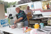 Bob Merrill and John Polasek with the tongs, prepare Otto Kaak's signature brats for the grill.