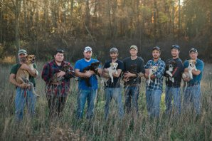 From left to right, Mitchel Craddock's groomsmen holding the puppies they brought back from Tennessee: Doug Craddock, holding the mom named Annie; Trevor Jennings, Gunner; Jake Rowe, Knox; David Perkins, Daisy; Logan Wolf, Bear; Mitchel Craddock, Brimmie; Brent Witters, Finn; and Alex Manchester, Rosie. Photo by Britnie Langs Photography.