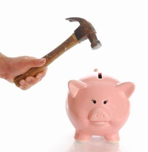 400-04685506 © willeecole Model Release: No Property Release: No man holding hammer aiming for pink piggy bank money box with reflection on white background