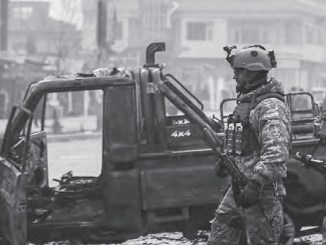 Afghan security force members walk past a bombed truck in Kabul (AFP photo by Zakeria Hashimi)