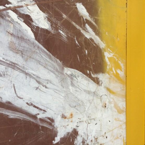 Kunstvolle Farbkleckerei in Weiß auf rotbrauner Containerwand mit gelbem Rand