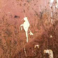 Taubenschiss in Form eines pinkelnden Mannes auf rostbrauner Conainerwand