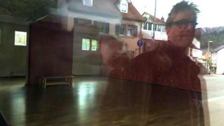 Spiegelung, in ein Schaufenster mit leerem Galerieraum fotografiert, außen sieht man Irgendlink, Häuser und Tafeln