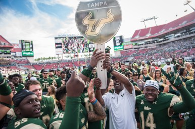 102 - USF vs. UCF 2016 - USF Head Coach Willie Taggart raises #WarOnI4 Trophy by Dennis Akers | SoFloBulls.com (6016x4016)