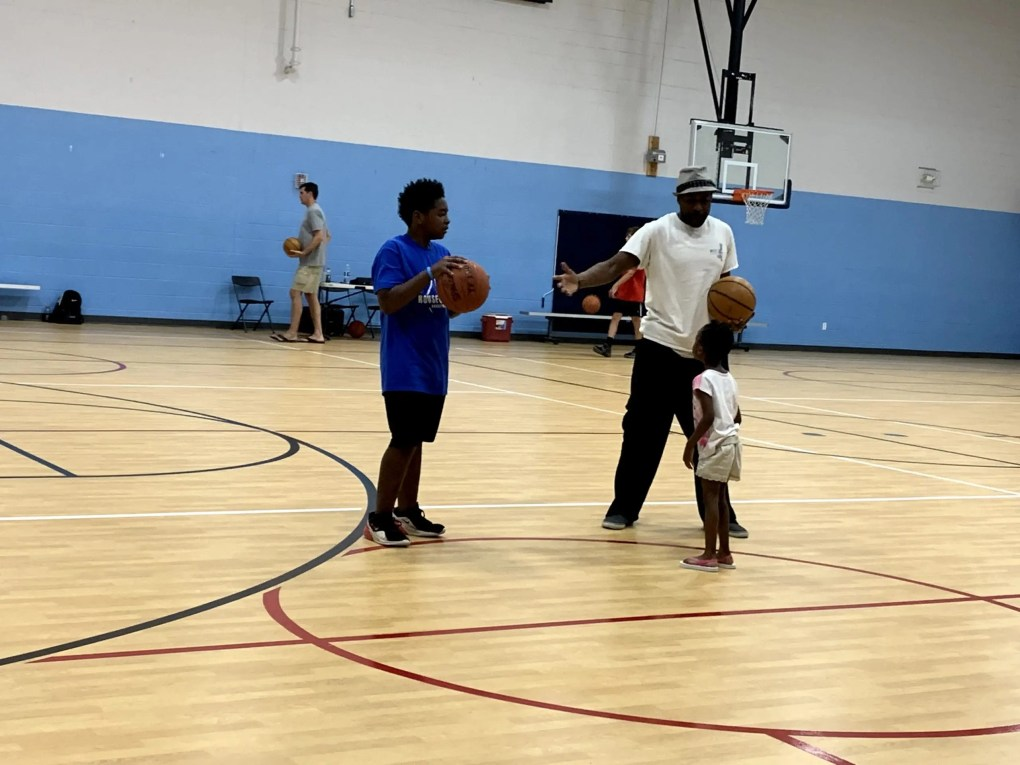 Man and teenager hold basketball while facing little girl.