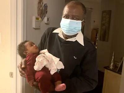 Elder man holding infant