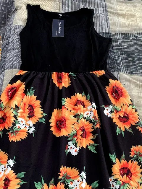 Black topped sleeveless maxi dress with bright sunflowers on the skirt