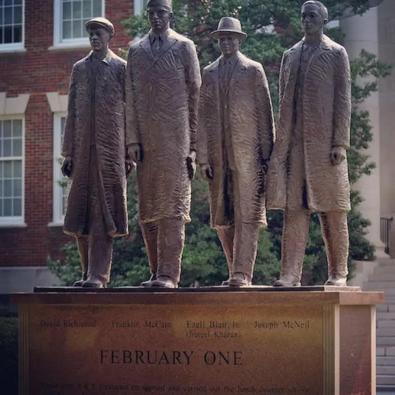 A brass statue of four men walking