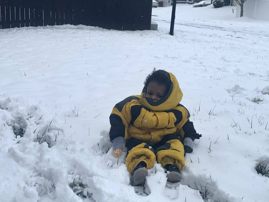 Toddler boy wearing a yellow snow suit sitting in snow staring at the camera.