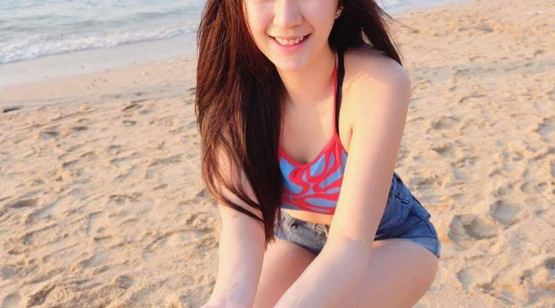cute thai girl sits on the beach