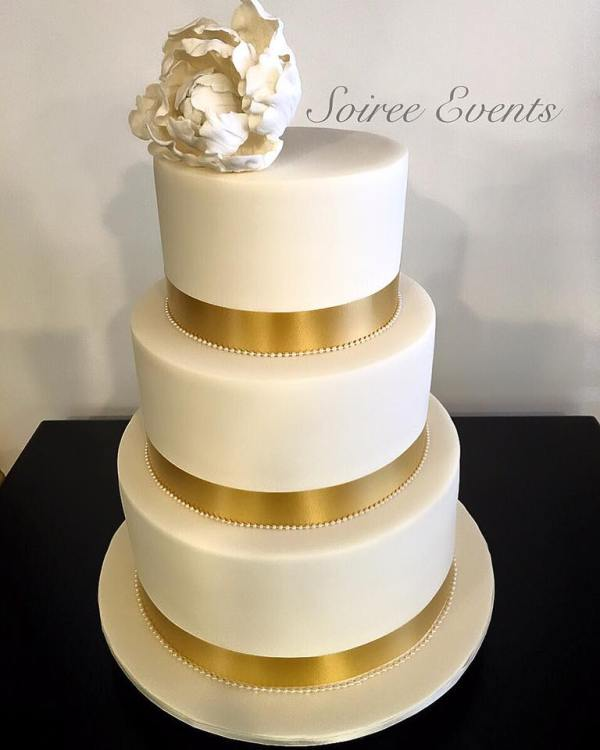 white wedding cake with gold ribbon and acrylic pearl trim