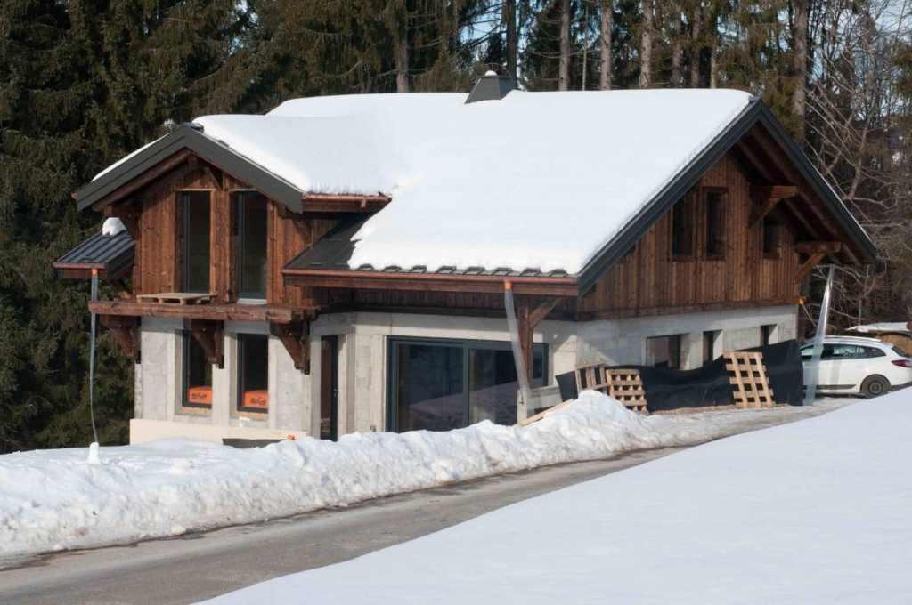 Chalet sous la neige avec bardage en bois brûlé brossé et soubassement en pierre