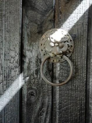 Raie de lumière sur ce lion en bronze fixé sur le bardage shou sugi ban à l'entrée de notre maison en bois brûlé