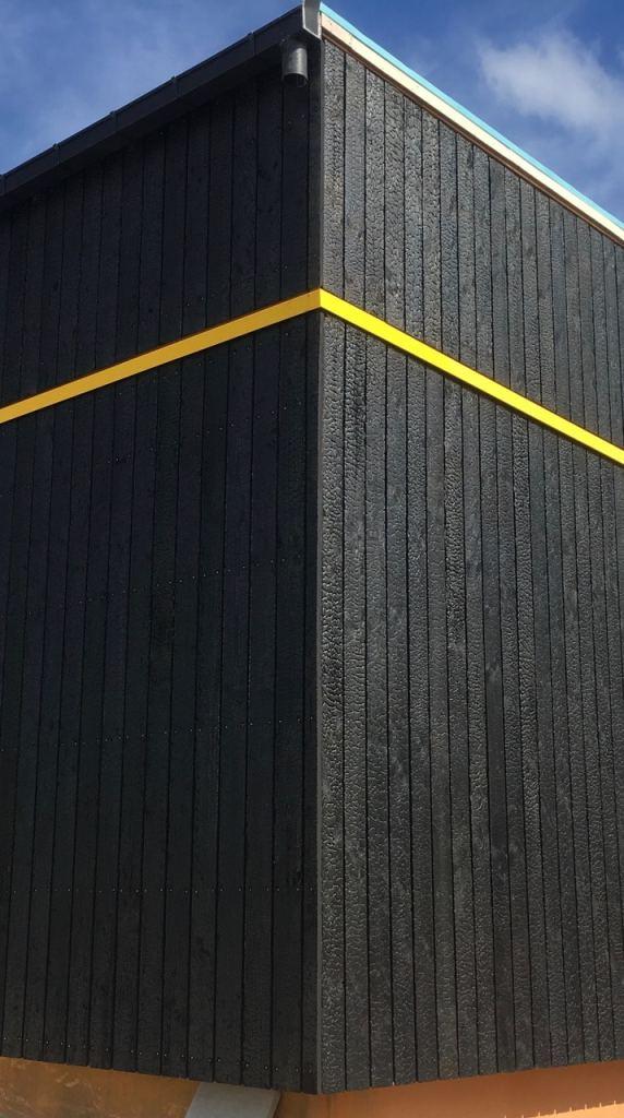 Angle de batiment en bois brûlé avec une ligne jaune