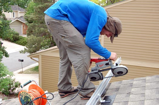 Tim saws off excess railing. Tim's job often requires that he complete difficult work right at the edge of a roof.