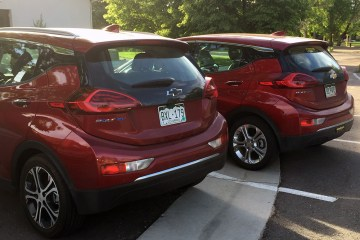 Two red Chevy Bolts parked next to each other.