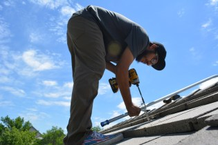 Vincent installs steel conduit casing on the Common House north roof.