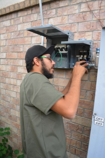 Shane installs a solar switch box on the garages on Day 7.