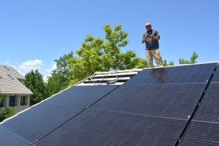 Shane waits for the final solar panel to be carried up to the roof by Vincent.