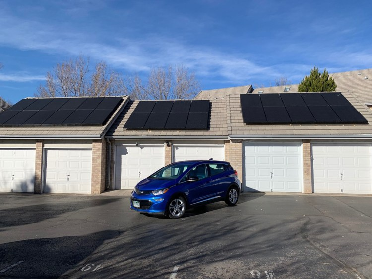 a solar EV in front of a garage with solar panels