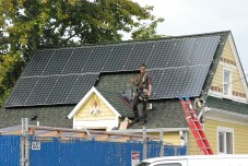worker on roof installing solar panels