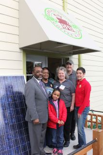 People assembed outside of Clean Greens with solar panel