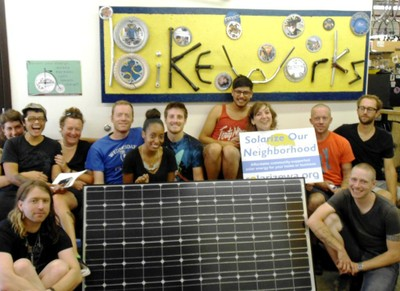 Staff of Bike Works sitting beside one of the solar modules donated to their bike shop