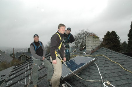 City Council member Mike O'Brien installing solar panels in Capitol Hill