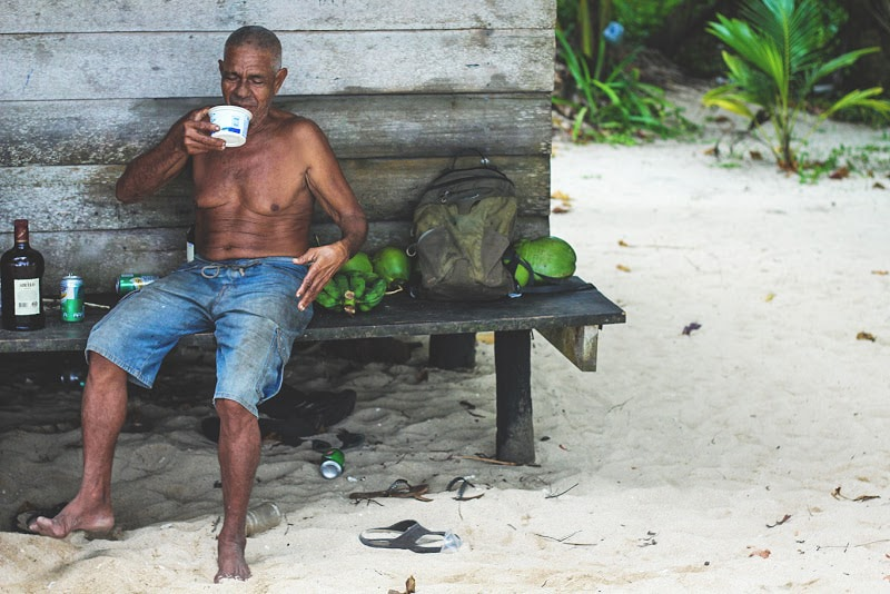 Man from isla bastimentos drinks out of plastic container in front of this local style hut on Polo Beach on isla bastimentos
