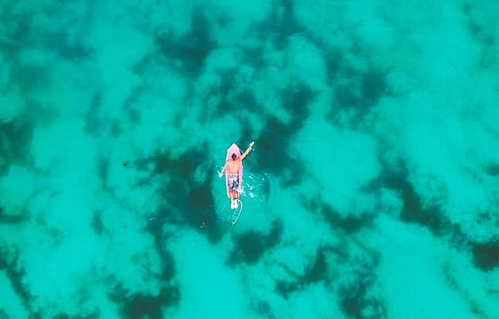 a man paddles on a surfboard on clear turquoise waters in bocas del toro panama