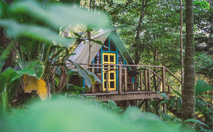 A colorfully painted tree house in the jungles of Isla Colon in Bocas del Toro from Nomad Tree Lodge.