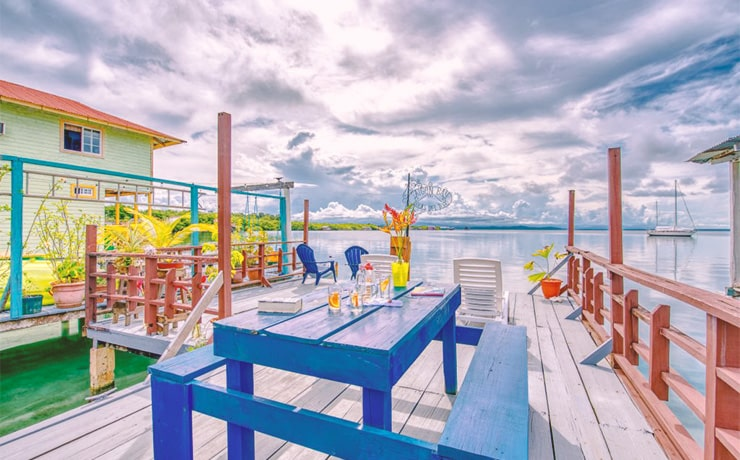 The overwater deck of Saigon Bay B&B in Bocas del Toro, Panama, with view of the ocean, a cloudy sky, and brightly painted wood buildings.