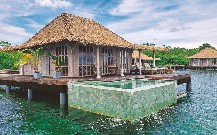 Bocas Bali overwater bungalow with plunge pool and thatch roof in Bocas del Toro, Panama.