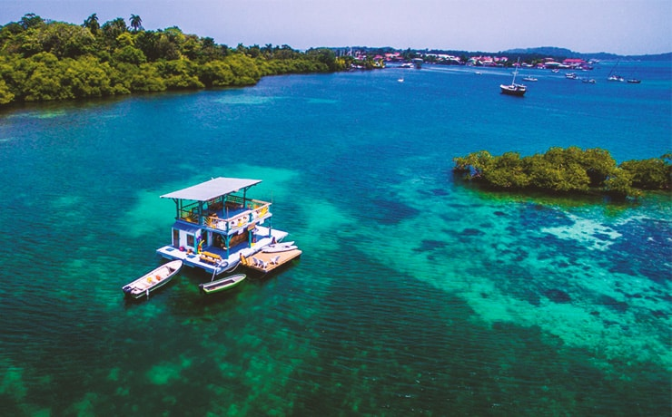 Drone view of the floating bar in bocas del toro with clear blue/green water and bocas town in the background.
