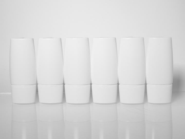 6 white tubes lined up across a white surface