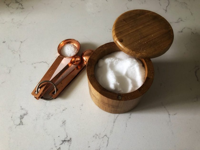 An open bamboo salt container sitting on the counter next to measuring spoons with salt.