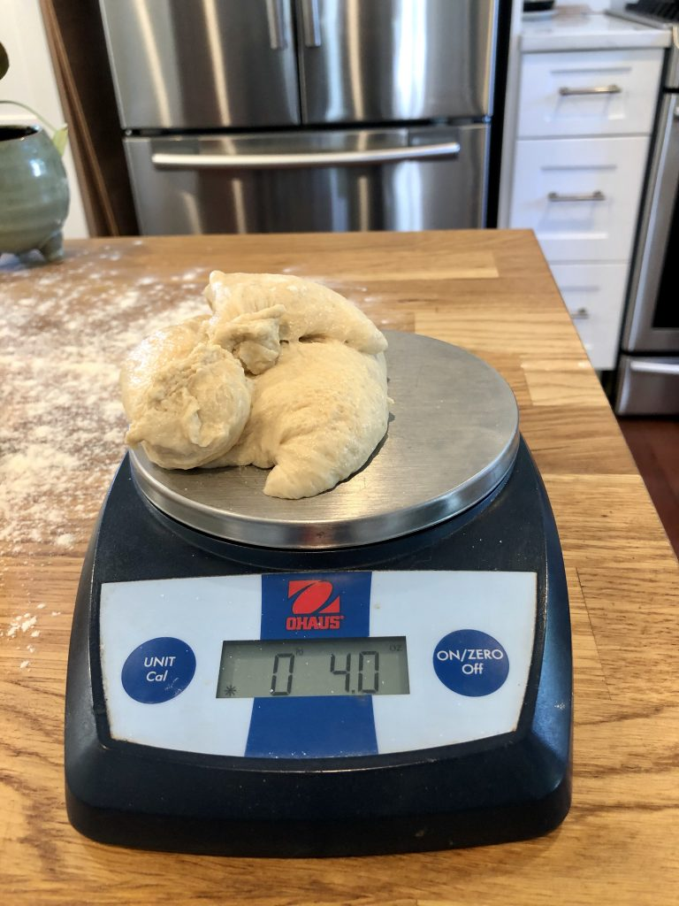 A food scale with dough on top measuring at 4 ounces.