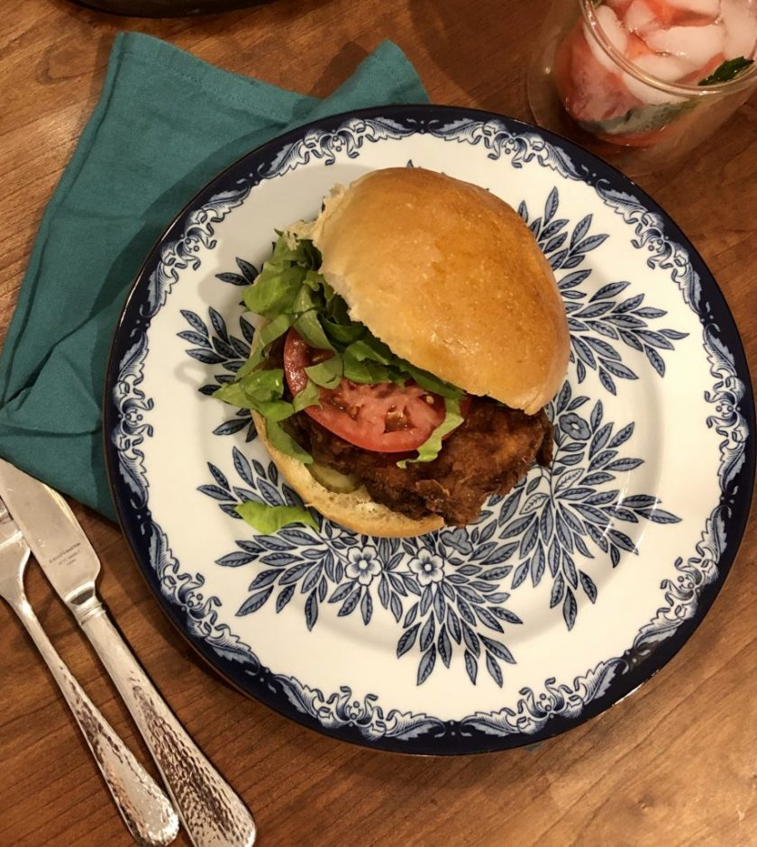 A fried chicken sandwich on a soft sandwich roll with lettuce and tomato on a blue floral plate with a fork, knife and cloth napkin.