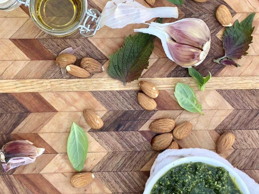 A bowl of pesto on a cutting board with whole garlic cloves, almonds, basil and shiso leaves and a container of olive oil.