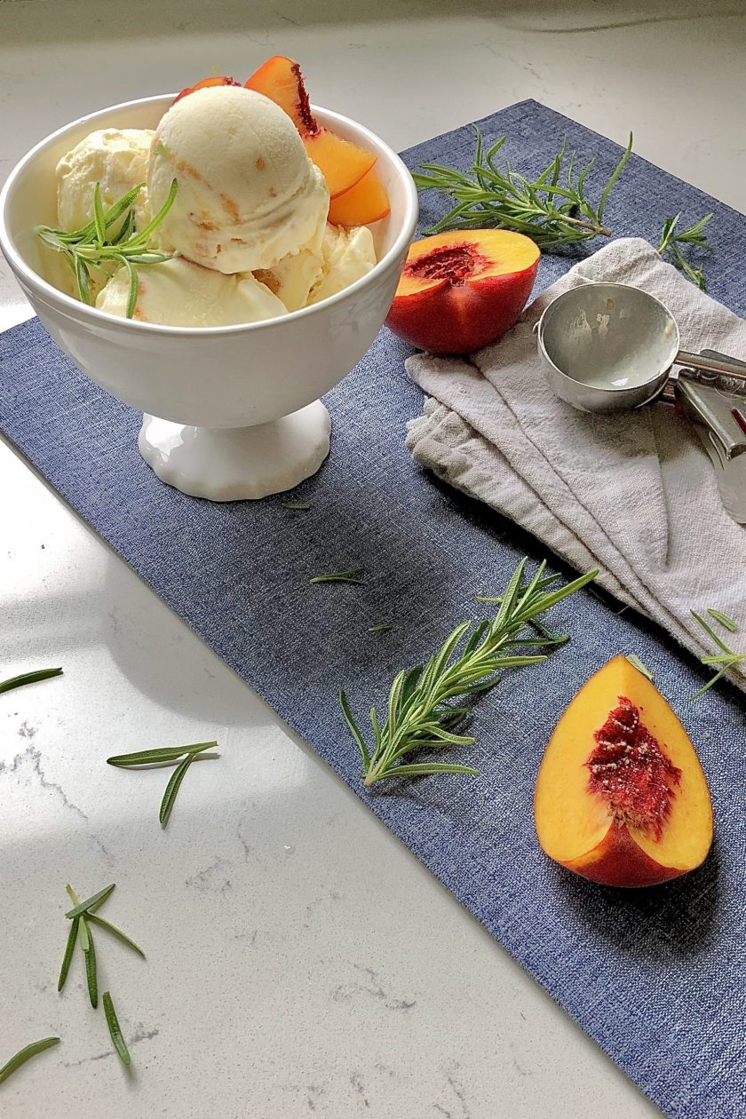 Roasted peach and rosemary ice cream in a bowl on the countertop with peaches and fresh rosemary and an ice scream scooper.